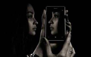 L'immagine mostra una ragazza che si specchia virtualmente in uno smartphone